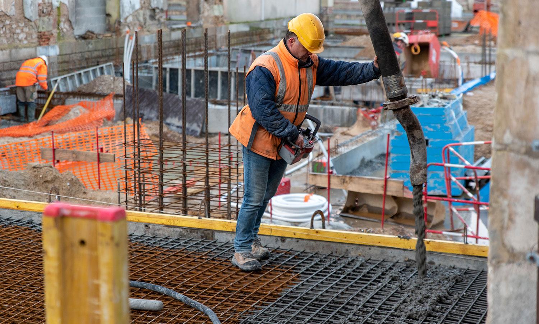 Un ouvrier coule le beton pour les sols du chantier